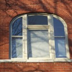 These arched-top storm windows have a changeable screen/storm panel on the lower half.